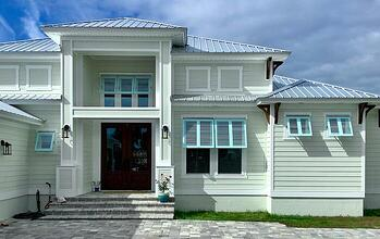 House with blue exterior Bahama shutters