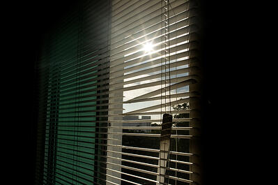 broken blinds in dark room with sun shining in